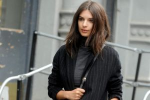 Supermodel Emily Ratajkowski looks fierce in a short skirt with a pinstripe trench and boots for a DKNY photo shoot ...