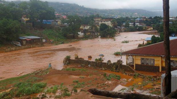 A torrent of water flows through a flooded neighbourhood in Regent, east of Freetown, Sierra Leone, on Monday.