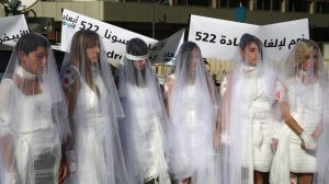 In this December 6, 2016 file photo, Lebanese women, dressed as brides in white wedding dresses stained with fake blood, ...