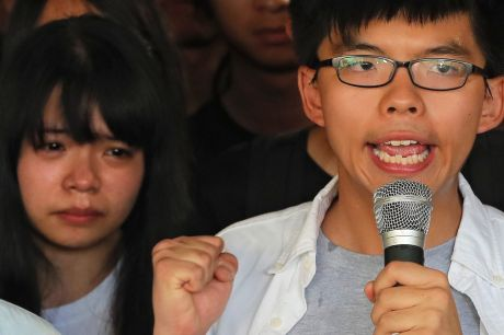 Joshua Wong, right, chants slogans as a supporter, left, reacts outside the high court before a ruling on a prosecution ...