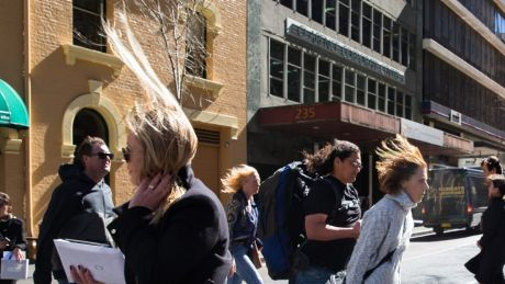 Pedestrians in Sydney struggle in the windy conditions.