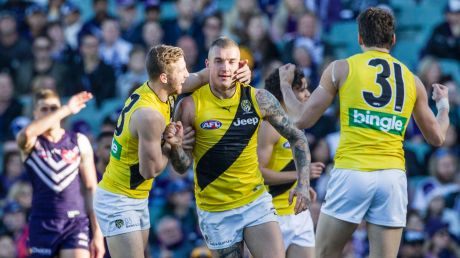 Richmond celebrate with Daniel Rioli of Richmond during the round 22 AFL match between the Fremantle Dockers and the ...