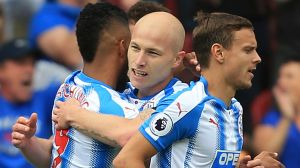 Huddersfield Town's Aaron Mooy, centre, celebrates with teammates after scoring his side's first goal during their ...