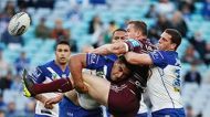 Brenton Lawrence of the Sea Eagles is tackled by Danny Fualalo and Adam Elliott of the Bulldogs during the round 24 NRL ...