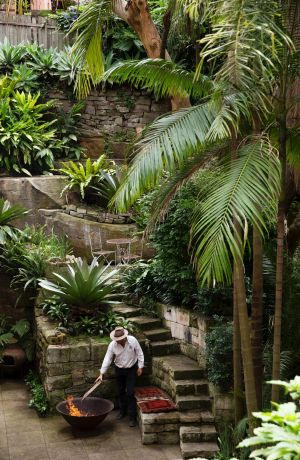 Michael Bates tends a fire pit among the towering palms of his lush garden.