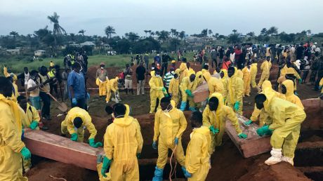 Volunteers handle coffins during a mass funeral for victims of heavy flooding and mudslides in Regent at a cemetery in ...