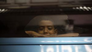 A boy looks out the window of a private bus used by Mexican authorities to transport a large group of Central American ...
