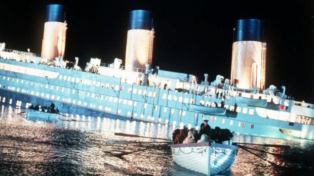 Passengers row to safety aboard a lifeboat as the ill-fated ship sinks in <i>Titanic</i>.
