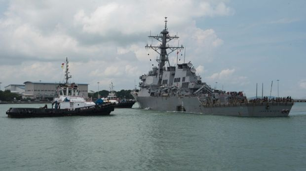 Tugboats from Singapore assist USS John S. McCain as it steers towards Changi Naval Base.