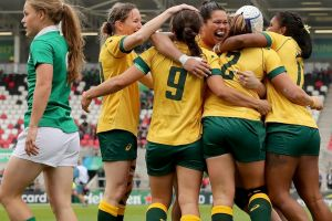 Australia captain Sharni Williams celebrates with her team-mates after scoring the opening try.