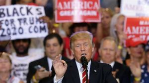 President Donald Trump speaks at a rally at the Phoenix Convention Centre.- a 'Blacks for Truth' sign in the background.