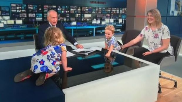 Toddler Iris Wronka tests her climbing skills on the studio desk