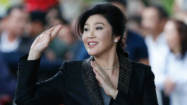 Former Thai prime minister Yingluck Shinawatra waves to supporters as she arrives at the Supreme Court for her final ...