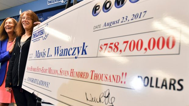 A Powerball lottery winner and her cheque in Massachusetts in August 2017.