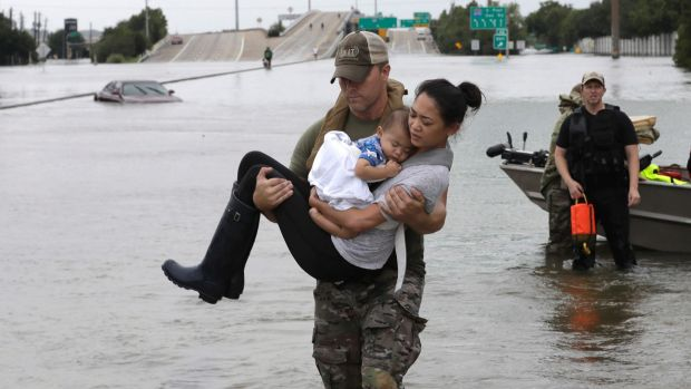 Houston Police SWAT officer Daryl Hudeck carries Connie Pham and her 13-month-old son Aiden after rescuing them from ...