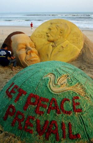 Indian artist Sudersan Pattnaik gives final touches to a sand sculpture of  Barack Obama at Golden Sea Beach in Puri.