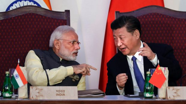 Indian Prime Minister Narendra Modi, left, talks with Chinese President Xi Jinping at the BRICS summit in Goa, India, ...