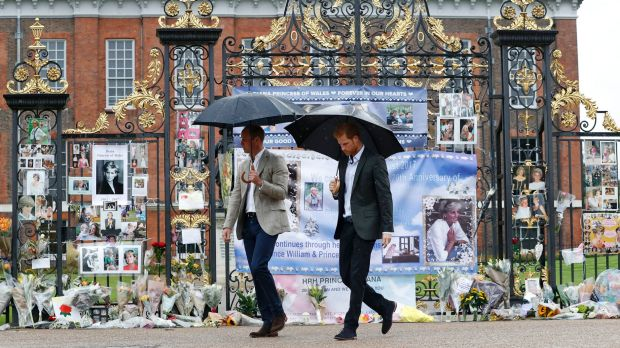 Britain's Prince William, left, and Prince Harry visit tributes to their late mother placed on the gates of Kensington ...