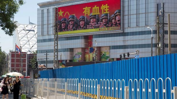"People walk near a billboard of the Chinese military reading ""courageous"", in Beijing, last month. Beijing is ..."