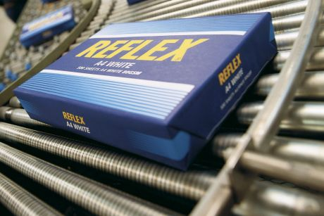Packages of Reflex brand copier paper roll along a production line.