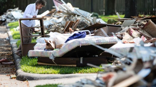 A resident views her flood-damaged possessions piled in the front yard in the aftermath of Hurricane Harvey in Houston.