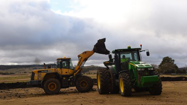 A front end loader moves biosolids to be spread on paddocks on the sheep property Ferndale, NSW.