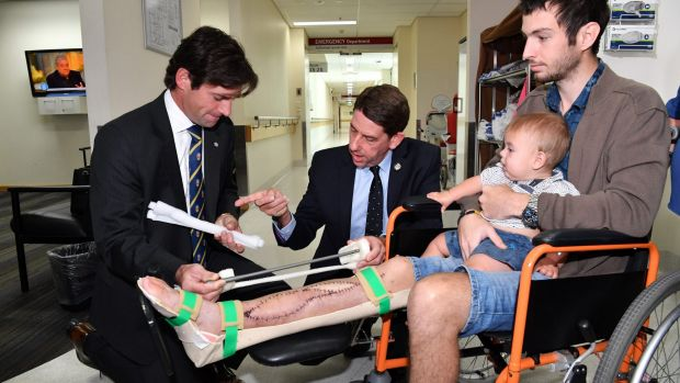 Surgeon Dr Michael Wagels and Queensland Health Minister Cameron Dick discuss the operation with Reuben Lichter and his ...