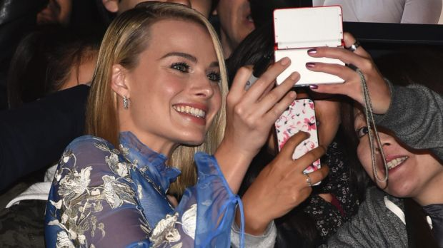 Margot Robbie takes a selfie with fans at the premiere in Toronto.