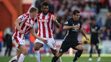 Stoke City's Eric Maxim Choupo-Moting, center, and Manchester United's Henrikh Mkhitaryan, right, battle for the ball ...
