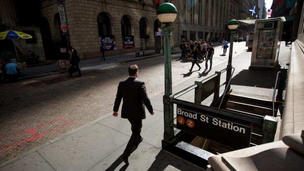 A pedestrian walks along Wall Street near the New York Stock Exchange.