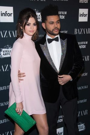 Selena Gomez, left, and Abel Tesfaye, known professionally as The Weeknd, attend the Harper's BAZAAR 'Icons by Carine ...
