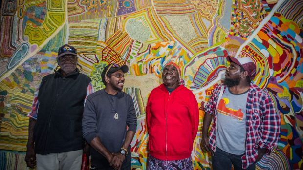 Muuki, Ignatius, Nola and Curtis Taylor stand in front of the painting Yarrakalpa.