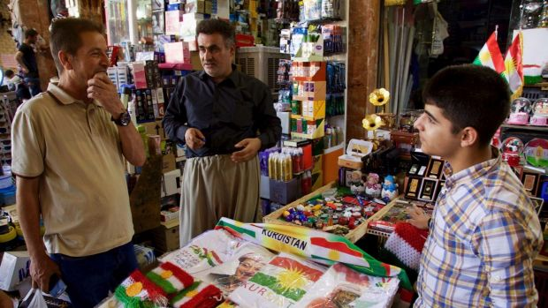 A salesman in Irbil's bazaar selling patriotic and pro-independence ware talks with a customer in Irbil Iraq