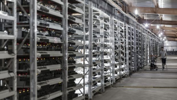 A technician inspects bitcoin mining machines at a mining facility in China.