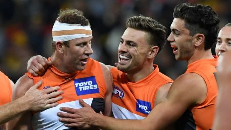 How the west was won: The Giants celebrate with veteran Steve Johnson (centre) after thrashing the Eagles.