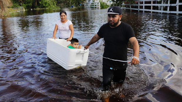 Alfonso Jose pulls his son, 2,in a cooler with his wife as they wade through floods in Florida.