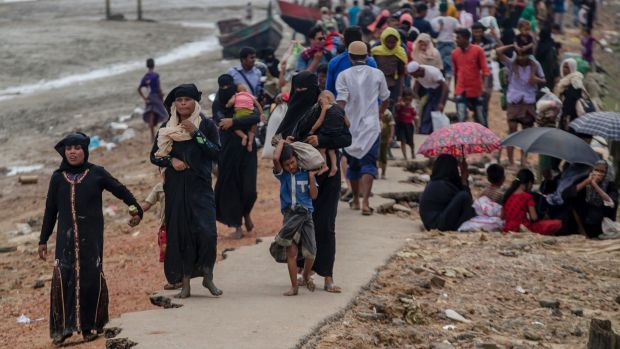 Rohingya Muslims who crossed over from Myanmar into Bangladesh walk towards the nearest refugee camp at Teknaf