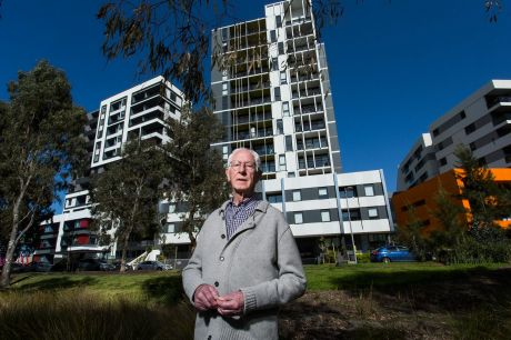 Parkville resident Joe Edmonds in front of an 11-level tower on the former Commonwealth Games Village site. New rules ...