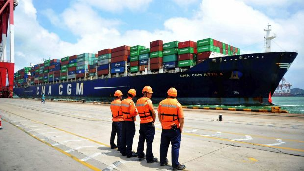 Port workers wait for a container ship as it docks at a port in Qingdao.