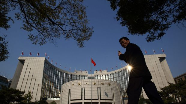 A pedestrian walks past the People's Bank Of China (PBOC) headquarters.