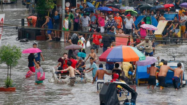 Residents wade through flood waters following overnight rains brought about by typhoon Talim inundated low-lying areas ...