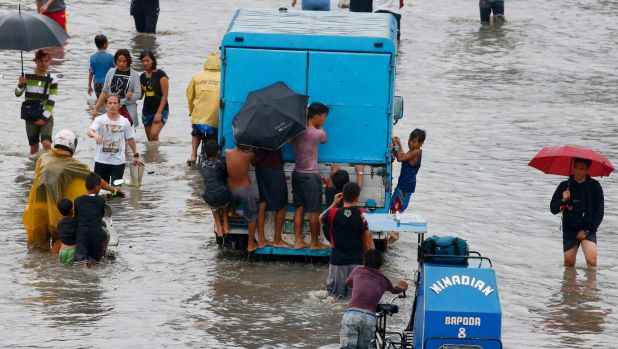 Boys cling to a delivery van as others wade through the floods after Talim brought heavy rains to Manila, Philippines.
