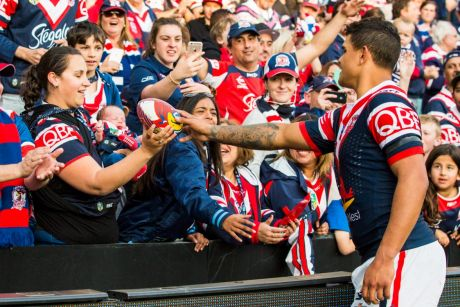 Last man: Latrell Mitchell giving a Roosters football to a new mum for her baby.