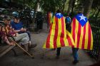Two men watch pro independence supporters passing by as they gather in support for the secession of the Catalonia region ...
