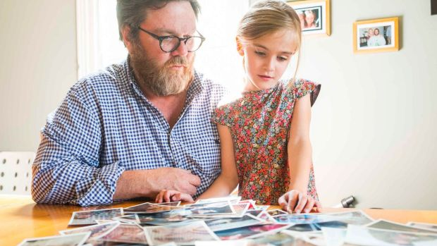 Elsie Ryan, 5, looks at family snaps of her late mother Campbel Giles with her father Matt Ryan.