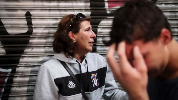A woman and her son take cover as Spanish National Police storm Barcelona's Ramon Llull school, which the Catalan ...