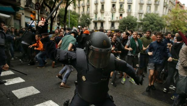 A Spanish riot police officer swings a club at would-be voters in Barcelona.