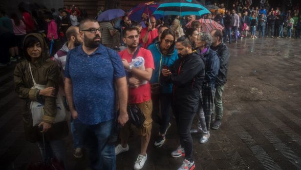 People in Barcelona queue in the rain to vote in the Catalan government referendum.