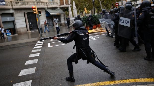 Spanish police in Barcelona shoot rubber bullets at people visiting a Catalan polling station.