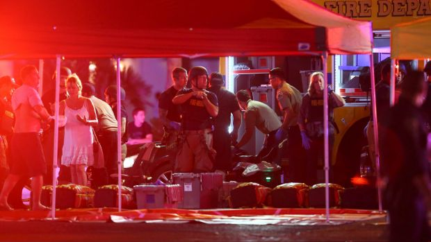 Medics treat the wounded as Las Vegas police respond to a shooting on the Las Vegas Strip on Sunday.